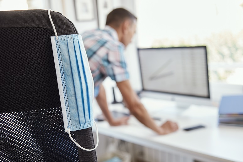 Man working in office with mask hanging from chair