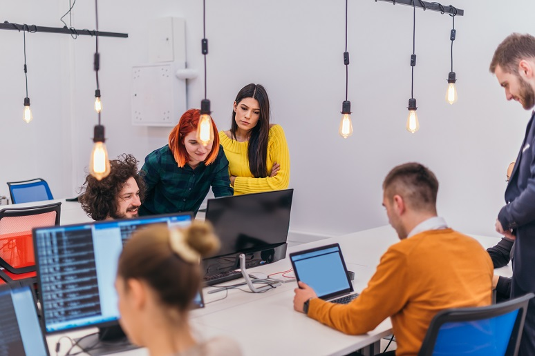 Photo shows group of young professionals collaborating in an office