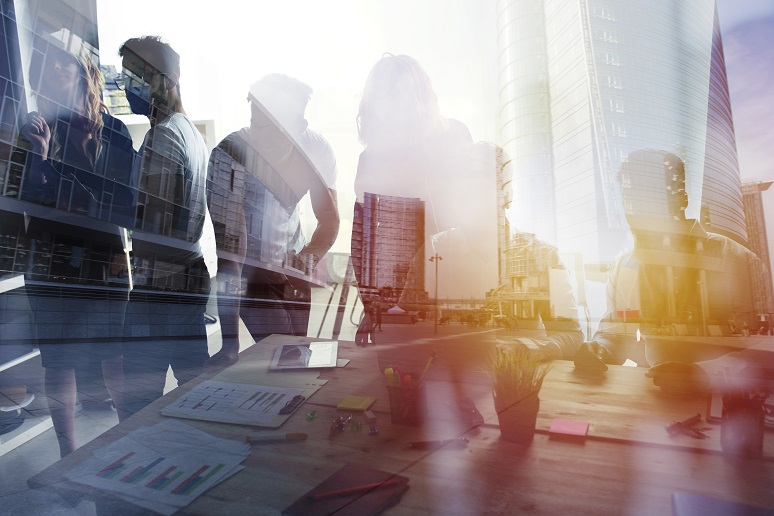 Photo illustration showing business leaders talking over reports with building in background