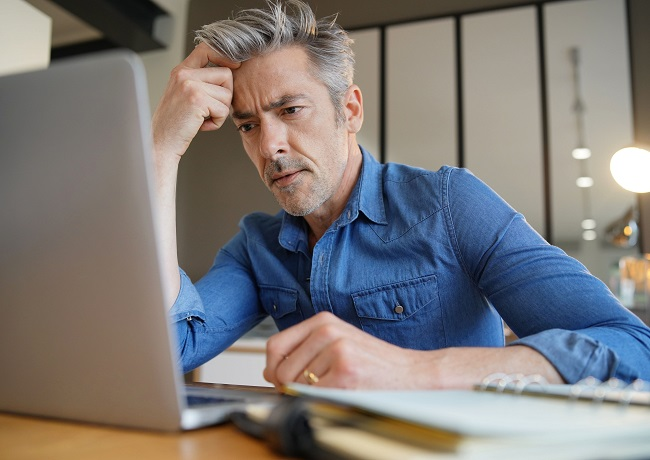 Gray haired man working from home