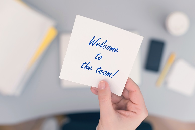 Photo of a business woman holding up a post-it note reading Welcome to the Team