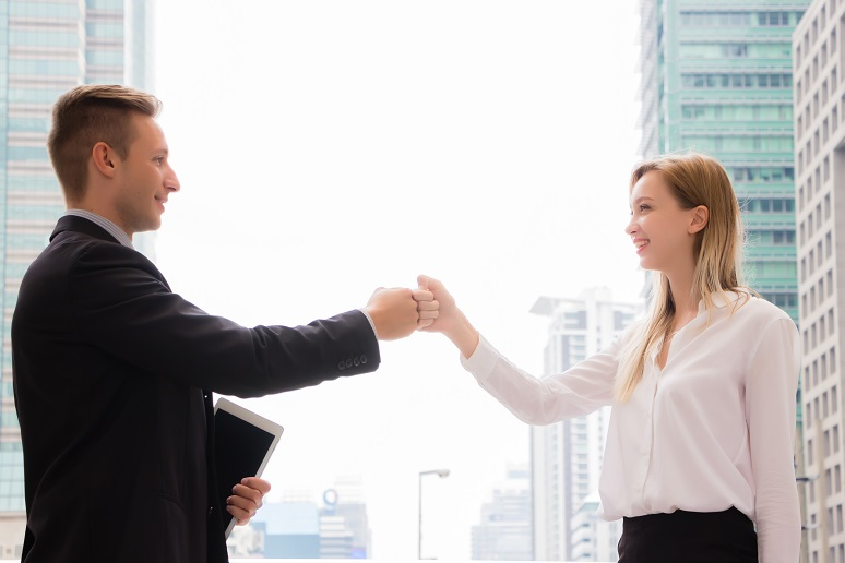 Two young business professional fist-bumping in the office