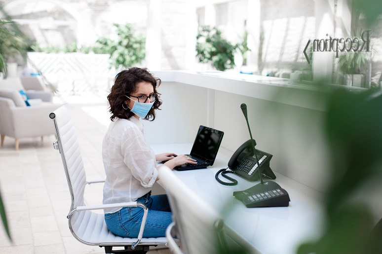 Receptionist wearing medical mask