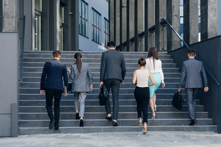 Picture of young business professionals walking up the steps to office building
