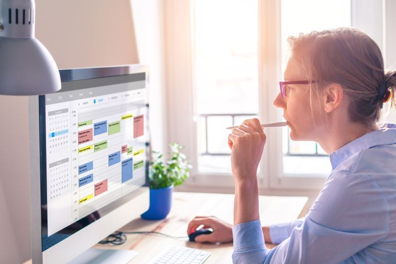 Business woman looking at overloaded meeting calendar