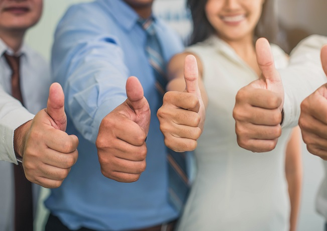 Photo of happy employees with thumbs-up