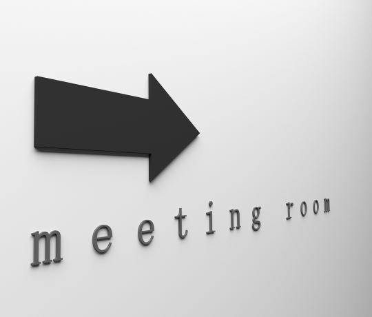 Photo of meeting room sign with arrow