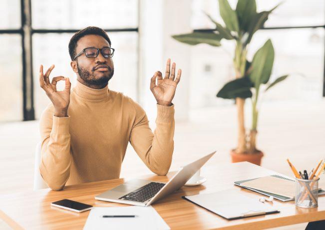 Photo of  man meditating at his desk to reduce stress