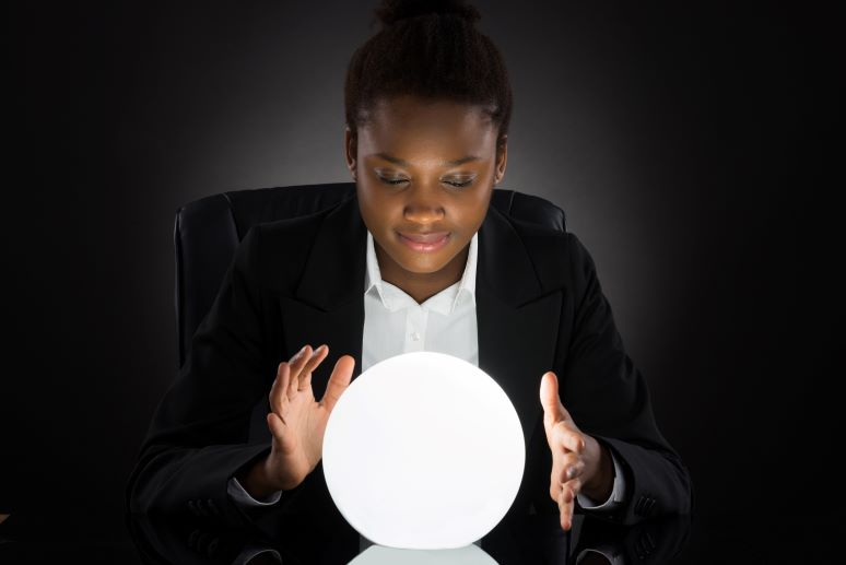 Young professional woman looking into crystal ball