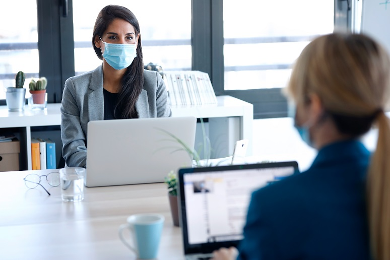 Two women professionals social distancing in the office