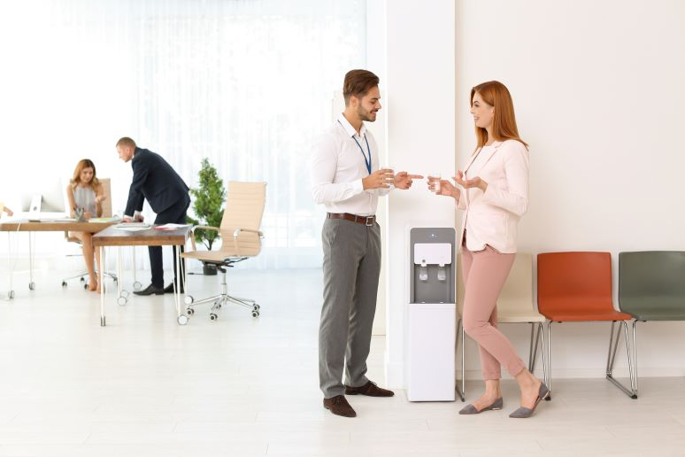 Business professionals chatting around a watercooler
