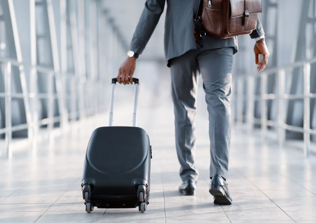 photo of businessman walking through airport