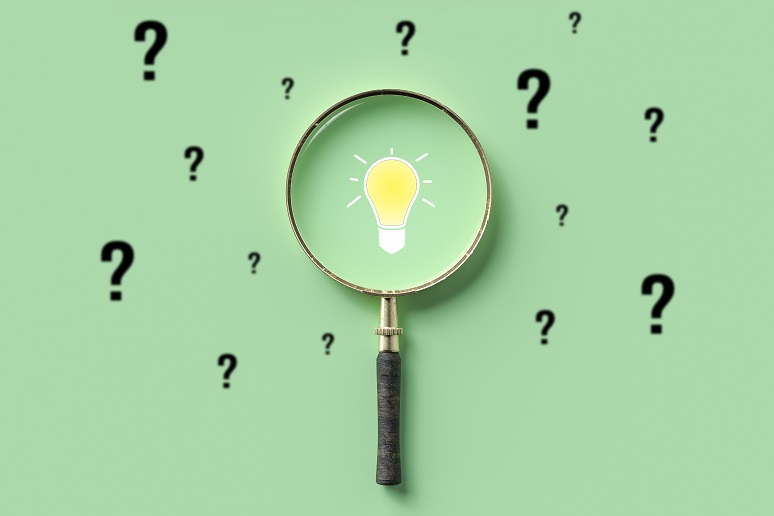 A magnifying glass on a light bulb surrounded by question mark